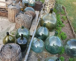 Old carboys of different sizes and from different eras in blown glass
