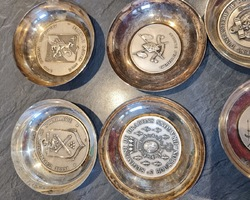 Silver metal cups with military medallions in the background of different regiment